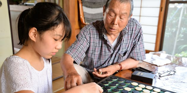 Granddaughter and grandfather playing Othello / Reversi, in cozy Japanese house.