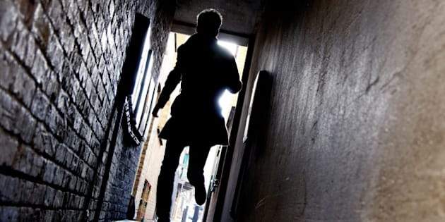 A mysterious running man silhouetted in a dark alleyway.