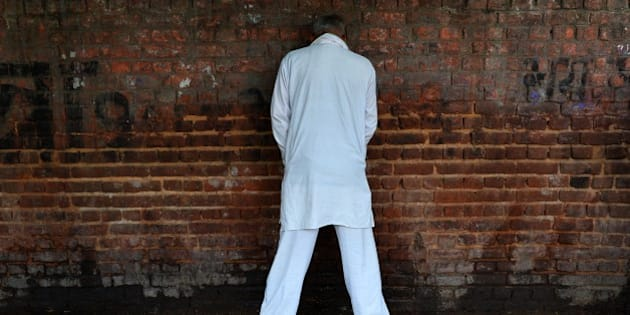 An Indian man urinates on a wall in New Delhi on November 18, 2014, the eve of World Toilet Day.  UNICEF estimates that almost 594 million -- or nearly 50 percent of India's population -- defecate in the open, with the situation acute in dirt-poor rural areas. Some 300 million women and girls are forced to squat outside normally under the cover of darkness, exposed not only to the risks of disease and bacterial infection, but also harassment and assault by men. AFP PHOTO/Chandan KHANNA        (Photo credit should read Chandan Khanna/AFP/Getty Images)