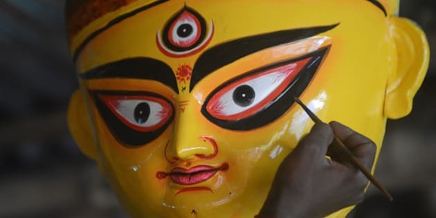 An Indian artisan paints a clay idol of Hindu goddess Durga inside his workshop in Kumartoli, the idol makers' village of Siliguri on October 13, 2015.  The five-day period of worship of Durga, who is attributed as the destroyer of evil, commences on October 18.    AFP PHOTO / Diptendu DUTTA        (Photo credit should read DIPTENDU DUTTA/AFP/Getty Images)