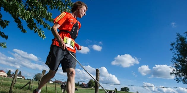 Clement Gass, who is nearly blind, runs the 26 km 'trail of Kochersberg' with a white cane and a GPS device using voice navigation in Quatzenheim, eastern France, on June 13, 2015. Gass, 27, ran the trail along with 219 other participants without the assistance of another athlete. AFP PHOTO / SEBASTIEN BOZON        (Photo credit should read SEBASTIEN BOZON/AFP/Getty Images)