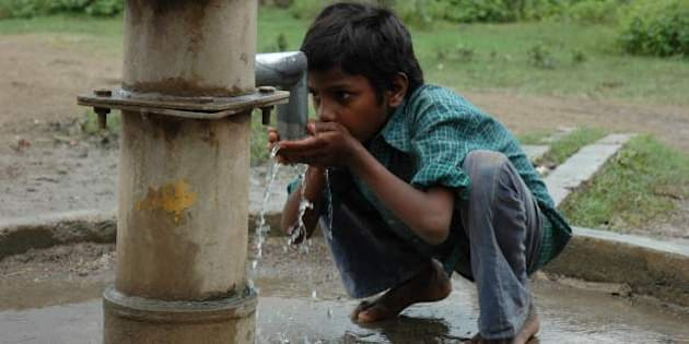 Boy drinking water from handpump in Guna, Madhya Pradesh - Handpumps and wells are still one of the major source of drinking water in India. Maintenance of aging handpumps is an issue to focus as they still are source of drinking water.