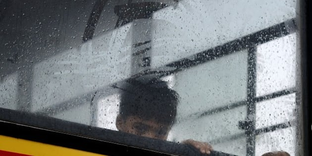 An Indian child looks out from his school bus in Faridabad on the outskirts of New Delhi on July 9, 2015, during heavy monsoon rainfall. AFP PHOTO/MONEY SHARMA        (Photo credit should read MONEY SHARMA/AFP/Getty Images)