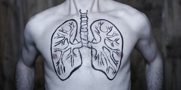 portrait of Man taking a large deep breath with lung illustration drawn on chest