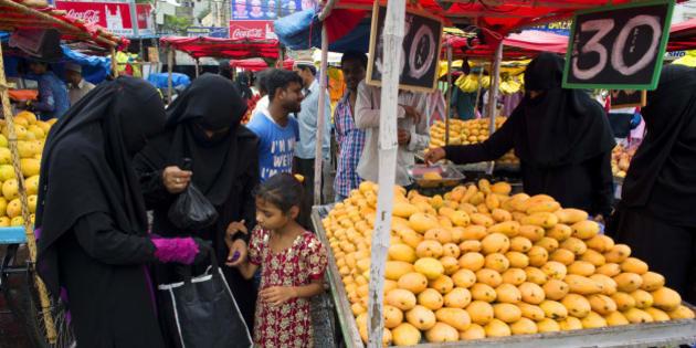 HYDERABAD, TELANGANA, INDIA - 2015/06/21: Muslim women in burqa buy fruits near Charminar during the holy month of Ramadan in Hyderabad. (Photo by Subhendu Sarkar/LightRocket via Getty Images)