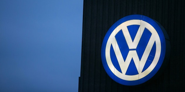 The VW logo sits illuminated on the exterior of the Volkswagen AG headquarters in Wolfsburg, Germany, on Tuesday, Oct. 13, 2015. VW Chief Executive Officer Matthias Mueller faced employees at the German company's headquarters last week as pressure mounts to slash spending in the wake of the diesel-emissions scandal. Photographer: Krisztian Bocsi/Bloomberg via Getty Images