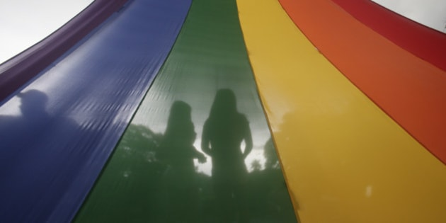 A LGBT (Lesbians Gays Bisexuals and Transgenders) couple is silhouetted by their rainbow-colored symbol while waiting to march around the University of the Philippines campus in an annual event to draw the attention to their issues as gay rights and anti-discrimination Friday, Sept. 11, 2015 at suburban Quezon city northeast of Manila, Philippines. More than a hundred LGBTs joined the march which culminated in a concert.(AP Photo/Bullit Marquez)
