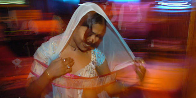 MUMBAI, INDIA:  In this picture taken late 06 May 2005, An Indian bar dancer dances with a garland of currency notes offered by a customer during a performance at a dance-bar in Mumbai.  The western Indian state of Maharashtra has decided to shut down 'dance bars' or drinking houses featuring scantily-clad dancers in the state capital which had escaped a state-wide crackdown last month. Some 1,500 dance bars operate in Maharashtra employing more than 100,000 women, most of whom style and ape their performances on elaborate Bollywood song-and-dance musical numbers for customers looking for food, liquor and entertainment while police claim that many of the bars double as pick-up joints.  AFP PHOTO/ Indranil MUKHERJEE  (Photo credit should read INDRANIL MUKHERJEE/AFP/Getty Images)