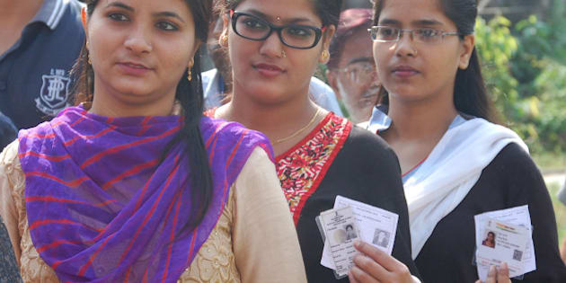 BHAGALAPUR, INDIA - OCTOBER 12: Voters pose with their cards for picture as they wait in a long queue to cast their votes during the first phase of Bihar Assembly polls, at Durgacharan High School on October 12, 2015 in Bhagalpur, India. An estimated 57 per cent of the electorate cast their votes in the first phase of Bihar Assembly elections in 49 constituencies which was violence-free note today. (Photo by Hindustan Times via Getty Images)