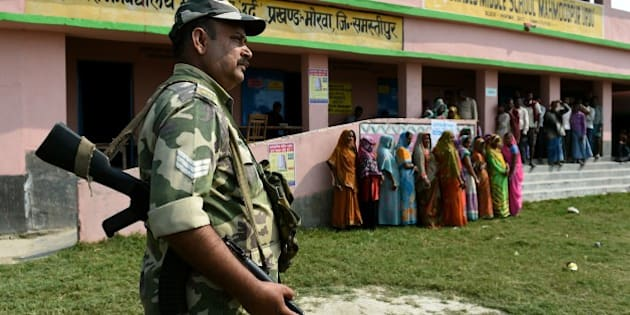 Indian voters queue to cast their ballots as security personnel stand guard at a voting centre in the village of Mahmoodpur in Samstipur district on October 12, 2015. The first of five phases of voting in the state assembly elections in Bihar, one of India's largest and poorest states, begins on October 12.  AFP PHOTO / MONEY SHARMA        (Photo credit should read MONEY SHARMA/AFP/Getty Images)