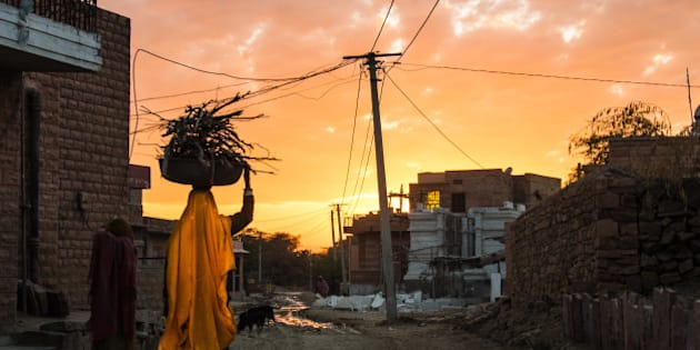 An indian Woman is carrying firewood - a romantic sunset in a less romantic scenery
