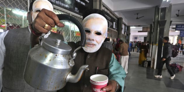 India's opposition Bharatiya Janata Party (BJP) workers wearing paper masks of their Prime Ministerial candidate Narendra Modi, sell tea at a railway station as part of their campaign for the upcoming parliamentary elections in Bhopal, India, Sunday, Jan. 26, 2014. (AP Photo/Rajeev Gupta)