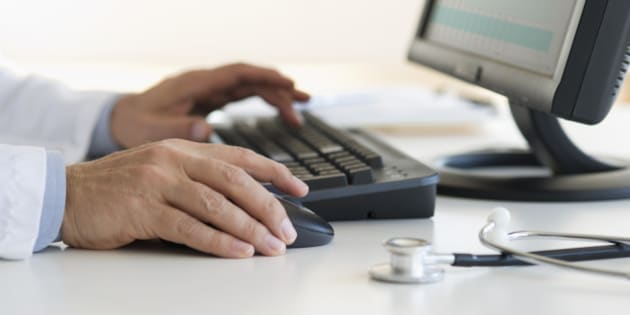 Male doctor's hands typing on desktop computer keyboard with stethoscope