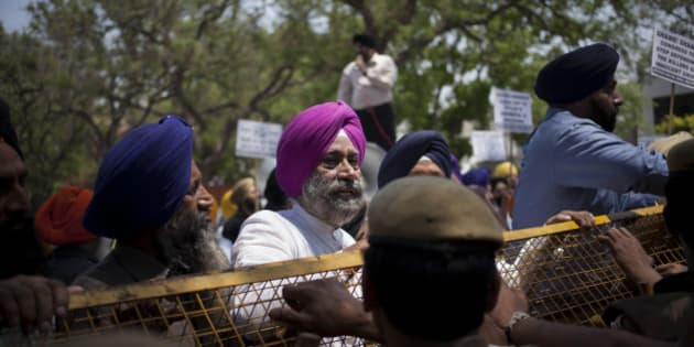 Indian Sikhs stand near a police barricade during a protest against Congress party leader and former chief minister of Punjab state Captain Amarinder Singh for his recent remarks on the country's 1984 anti-Sikh riots, in New Delhi, India, Monday, April 21, 2014. Singh in a recent television interview said party leader Jagdish Tytler, one of the accused, had no role in the 1984 riots that killed more than 3,000 Sikhs. Top Congress party leaders have been accused of inciting mobs during the violence that followed the assassination of Prime Minister Indira Gandhi by her Sikh bodyguards. (AP Photo/Tsering Topgyal)