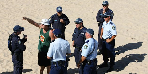 Police question a man on Cronulla Beach in Sydney, Australia, Sunday, Dec. 18, 2005. Cronulla is one of a number of Sydney beaches that is experiencing a high volume of police patrols, the largest security operation since  the Olympics, following a week of racial unrest. (AP Photo/Paul Miller)