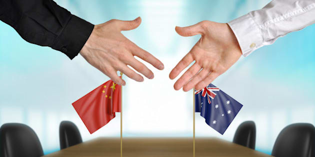 Two diplomats from China and Australia extending their hands for a handshake on an agreement between the countries.