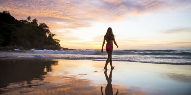 A woman walking in the sand on a tropical beach at sunset.