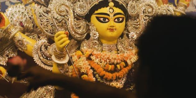 Pandit praying in front of goddess Durga, Kolkata, West Bengal, India