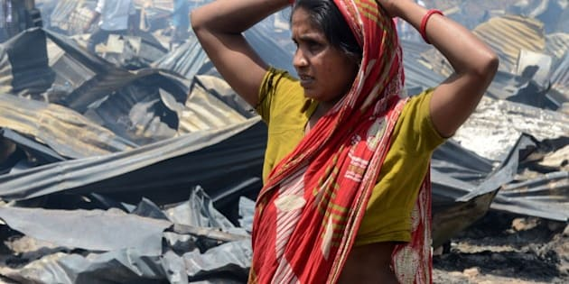 An Indian resident stands in front of the charred remains of her damagaed home after a fire broke out in a makeshift settlement in New Delhi on April 25, 2014. More than 600 homes were destroyed in the blaze. The cause of the fire is not yet known, fire department officials said.   AFP PHOTO/RAVEENDRAN        (Photo credit should read RAVEENDRAN/AFP/Getty Images)