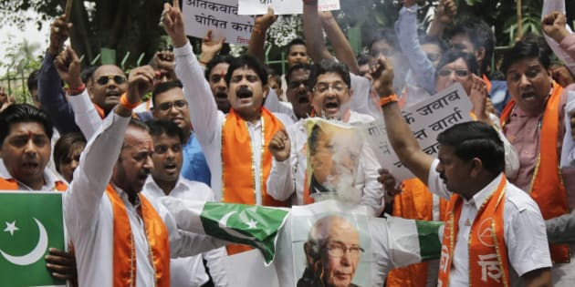 """Hindu right-wing Shiv Sena activists burn an effigy and pictures of Pakistani Prime Minister Nawaz Sharif, top, and Pakistan's Prime Minister's Adviser on Foreign Affairs Sartaj Aziz during a protest in New Delhi, Saturday, Aug. 22, 2015. From left to right, the banners in Hindi read: """"declare Pakistan terrorist state"""", """"destroy terrorist camps in Pakistan"""", """"no peace talks in response to bullets"""". Pakistan and India have a history of tense relations. They have fought two of their three wars over Kashmir since gaining independence in 1947. (AP Photo/Altaf Qadri)"""