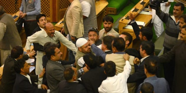 Independent lawmaker, Engineer Rashid (CL) shouts after being thrashed by Bhartiya Janta Party (BJP) legislators in the legislative assembly in Srinagar on October 8, 2015.  Independent lawmaker Engineer Rashid, who was thrashed by BJP legislators, said he had not indulged in any illegal act by hosting a beef party at his official residence on the evening of October 7.    AFP PHOTO/ Tauseef MUSTAFA        (Photo credit should read TAUSEEF MUSTAFA/AFP/Getty Images)