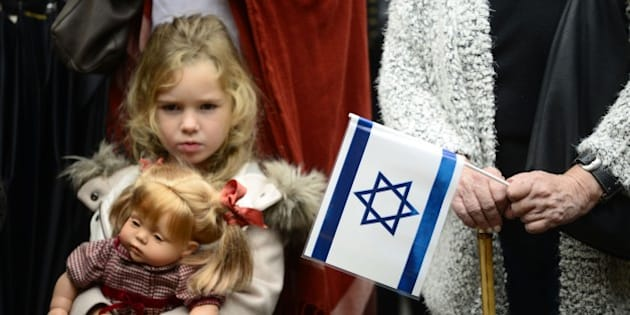 A young girl with her doll stands past a woman holding an Israeli flag and a Spanish flag during a rally in support of Israel called by Federation of Jewish Communities in Spain (FCJE) and the Jewish Community of Madrid, in front of the Israeli embassy in Madrid on October 18, 2015. Israel pressed ahead with major security measures after five more stabbing incidents, while ultra-Orthodox Jews illegally visiting a West Bank holy site set ablaze last week were assaulted by Palestinians.   AFP PHOTO/ PEDRO ARMESTRE        (Photo credit should read PEDRO ARMESTRE/AFP/Getty Images)