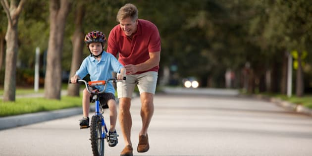 Father teaching son how to ride a bike