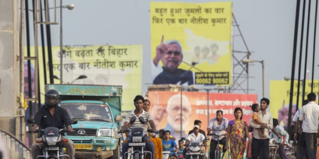 People ride motorcycles over a bridge past election billboard advertisements featuring images of Indian Prime Minister Narendra Modi and other party candidates in Patna, Bihar, India, on Monday, July 27, 2015. More than anywhere, Bihar reflects the challenge Prime Minister Narendra Modi faces in overhauling modern India. A vast, landlocked plain bordering the Himalayan nation of Nepal to the north and bisected by the Ganges, India's holiest river, the state is home to about one in 12 Indians. Photographer: Prashanth Vishwanathan/Bloomberg via Getty Images