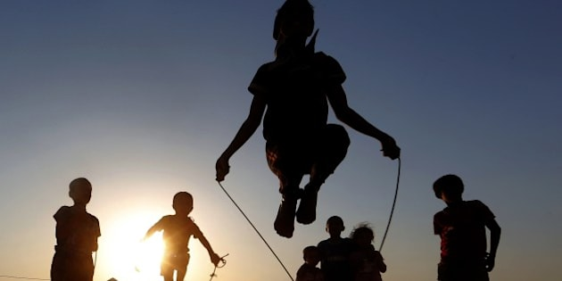 Iraqi displaced children play at sunset at a temporary camp set up to shelter people fleeing violence in northern Iraq on June 27, 2014 in Aski kalak, 40 kms west of the Kurdish autonomous region's capital Arbil.  AFP PHOTO/KARIM SAHIB        (Photo credit should read KARIM SAHIB/AFP/Getty Images)