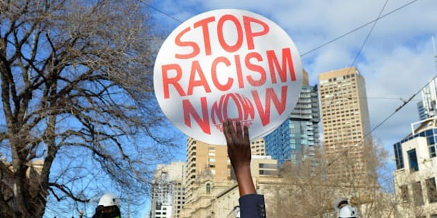 MELBOURNE, AUSTRALIA - JULY 18: An anti-racism activist holds up a placard as anti-Islam protesters stage rally in Melbourne, Australia on July 18, 2015. Hundreds of police were deployed in Western Australia on Saturday to break up violent protests near Parliament House in Melbourne after demonstrators from a right wing anti-Islam group faced off against anti-racism groups. (Photo by Recep Sakar/Anadolu Agency/Getty Images)