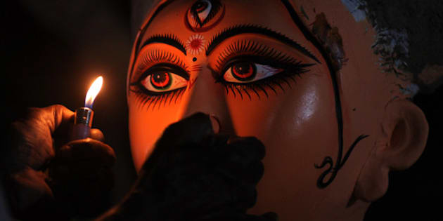 An Indian idol maker draws eyes onto a clay statue of Hindu goddess Durga, in Kumartoli, the idol makers village of Siliguri on September 29, 2011. Monsoon rain has made it difficult for artisans to finish idols on schedule and the recent economic slowdown and the high inflation is making the life difficult for these artist to do proper business ahead of this festive season. AFP PHOTO/Diptendu DUTTA (Photo credit should read DIPTENDU DUTTA/AFP/Getty Images)