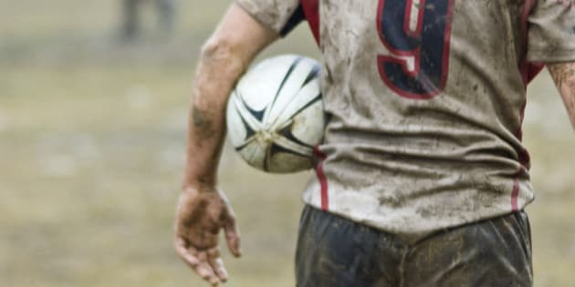 Rear view of bedraggled rugby player in rainy day,Spain.