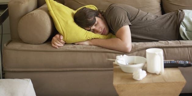 Young adult man sleeping on sofa