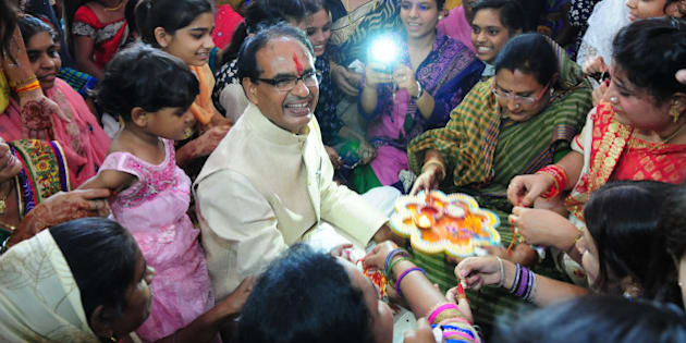 BHOPAL, INDIA - AUGUST 29: Women tying 'Rakhi' to the Madhya Pradesh Chief Minister Shivraj Singh Chouhan during a special Raksha Bandhan programme organised at CM house on August 29, 2015 in Bhopal, India. On Raksha Bandhan, sisters tie a rakhi (sacred thread) on her brother's wrist, which symbolizes the sister's love and prayers for her brother's well-being and the brother's lifelong vow to protect her. (Photo by Mujeeb Faruqui/Hindustan Times via Getty Images)