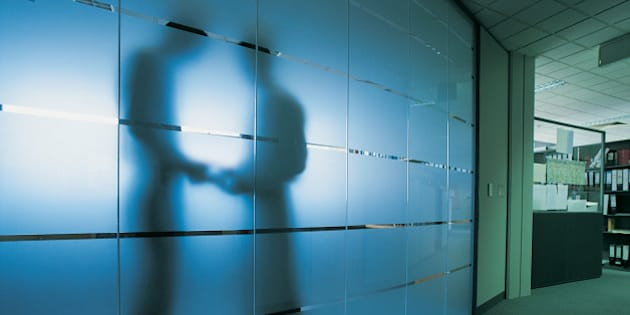Silhouette of a Businessman Standing Behind a Frosted Glass Window in An Open Plan office Receiving a Bribe From Another Businessman