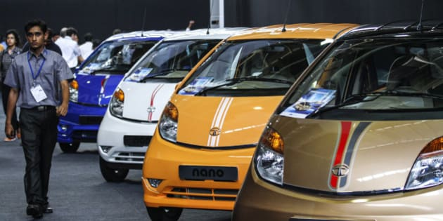 An employees walk past a line of Tata Motors Ltd. Nano automobiles on display during a media event in Pune, India, on Wednesday, June 19, 2013. Tata Motors announced the introduction of 8 new models today. Photographer: Dhiraj Singh/Bloomberg via Getty Images