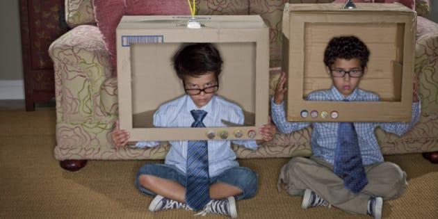 Boys dressed as businessmen sitting in cardboard televisions