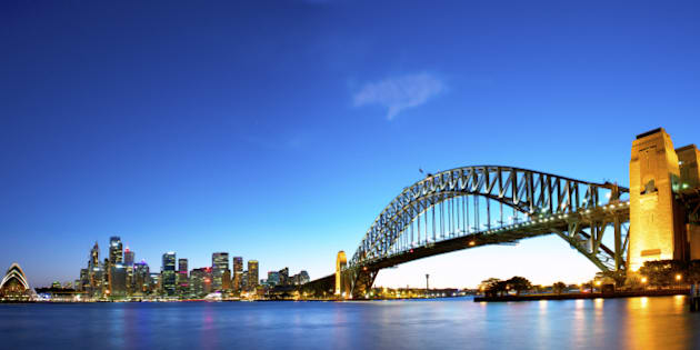 Panorama of Sydney Harbour with the opera house to the left, Financial district in the middle, and the harbour bridge to the right.
