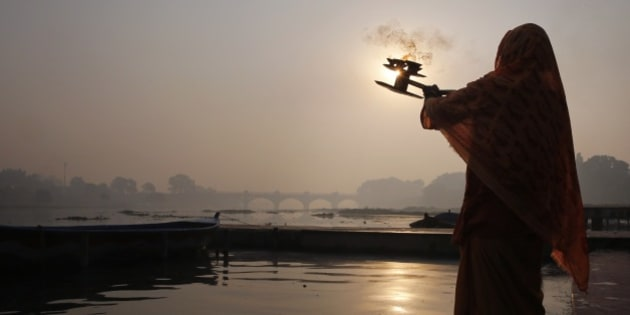 An Indian Hindu priest rotates a traditional oil lamp as he offers early morning prayers at the Kudia Ghat, or bathing steps that line along a river, on the banks of Gomti River in Lucknow, India, Thursday, Dec. 4, 2014. (AP Photo/Rajesh Kumar Singh)