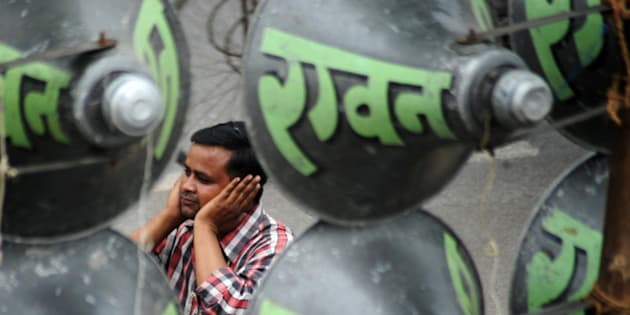 A Indian man protects his ears with his hands as he passes a display of 144 loudspeakers during a Dusshera festival loudspeaker competition in Allahabad on September 25, 2009. Playing loud music has traditionally been a part of local fairs in Allahabad, where owners of the sound system playing loudest are awarded. According to Indian Noise Regulation Rules set in 2000, permissible range for residential zones is 55 decibels. In addition, no permission can be granted by any authority for the use of public address system in the open after 10 p.m. and before 6 a.m.  AFP PHOTO/Diptendu DUTTA (Photo credit should read DIPTENDU DUTTA/AFP/Getty Images)