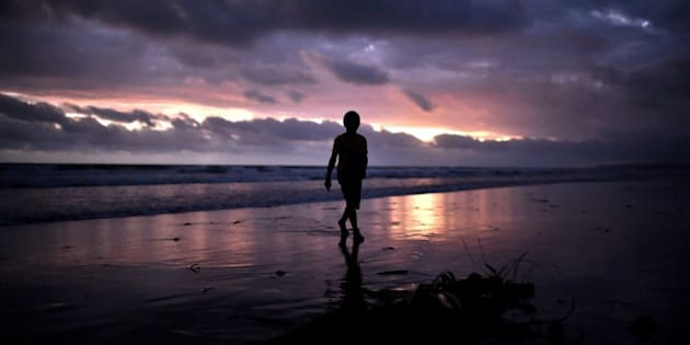 A young boy walks at sunset on the beach of Kerema, papua New Guinea, on September 9, 2014. AFP PHOTO / ARIS MESSINIS        (Photo credit should read ARIS MESSINIS/AFP/Getty Images)