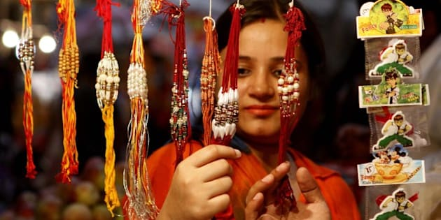 NEW DELHI, INDIA - AUGUST 28: A woman looks at 'rakhis' at a roadside shop on the eve of Raksha Bandhan, on August 28, 2015 in New Delhi, India. Celebrating the bond between brothers and sisters is the Hindu festival of Raksha Bandhan which will be celebrated across India and abroad on August 29. Sisters tie sacred Rakhi string on their brothers' right wrists and pray for their protection. (Photo by Virendra Singh Gosain/Hindustan Times via Getty Images)