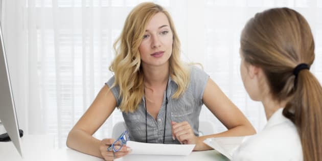 Blond haired businesswoman sitting at a desk opposite young woman and talking.