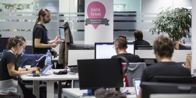 A data team sign sits on a pillar as employees work at desktop computers in the headquarter offices of BlaBlaCar, operated by Comuto SA, in Paris, France, on Friday, Sept. 25, 2015. Ride-sharing application BlaBlaCar has raised $200 million in funding, bringing the French company's valuation to $1.6 billion as it attempts to expand into new markets and help keep up with growth after its community of drivers more than doubled last year. Photographer: Christophe Morin/Bloomberg via Getty Images