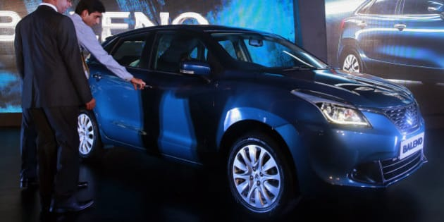 "People look at the newly-unveiled Baleno hatchback during its global launch in Mumbai, India, Monday, Oct. 26, 2015. India's largest carmaker Maruti Suzuki India (MSI) Monday rolled out its latest model ""Baleno"" which will be manufactured only in India and will be the first car from the MSI stable that will be exported to Japan, according to local reports. (AP Photo/Rafiq Maqbool)"