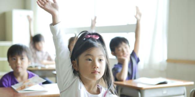 Schoolgirl (8-9) raising her hand