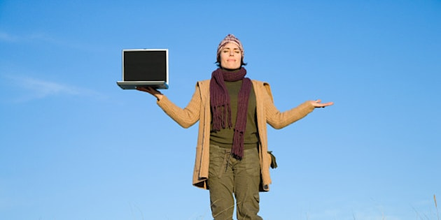 Serene woman in field with laptop