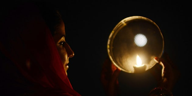 An Indian Hindu woman poses while performing a ritual on the occasion of the Hindu festival of Karva Chauth (Husband's Day) in Amritsar on November 2, 2012. Married women observe Karvachauth by fasting and offering prayers seeking welfare, prosperity, and longevity of their husbands. AFP PHOTO/ NARINDER NANU        (Photo credit should read NARINDER NANU/AFP/Getty Images)