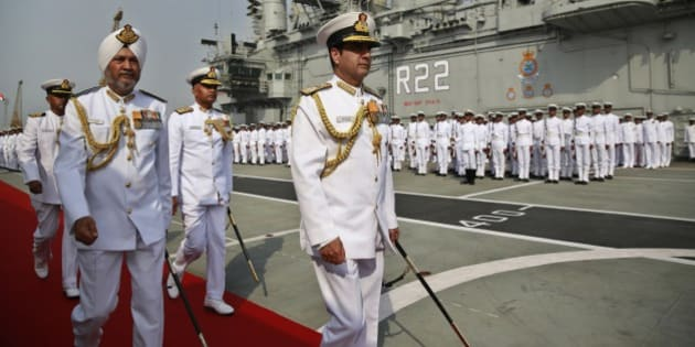 Indian Navy Chief Admiral R.K. Dhowan, center, along with chief of the Western Naval Command Vice Admiral S.P.S. Cheema, leave after participating in the Naval investiture ceremony held onboard the vessel INS Viraat at the Naval dockyard in Mumbai, India, Monday, April 20, 2015. (AP Photo/Rafiq Maqbool)