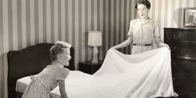 Mother and daughter making bed
